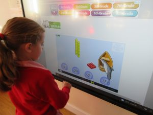 A school girl is helping with a task on the smart board in class