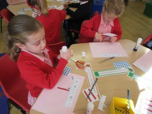 Children gluing numbers onto a piece of paper