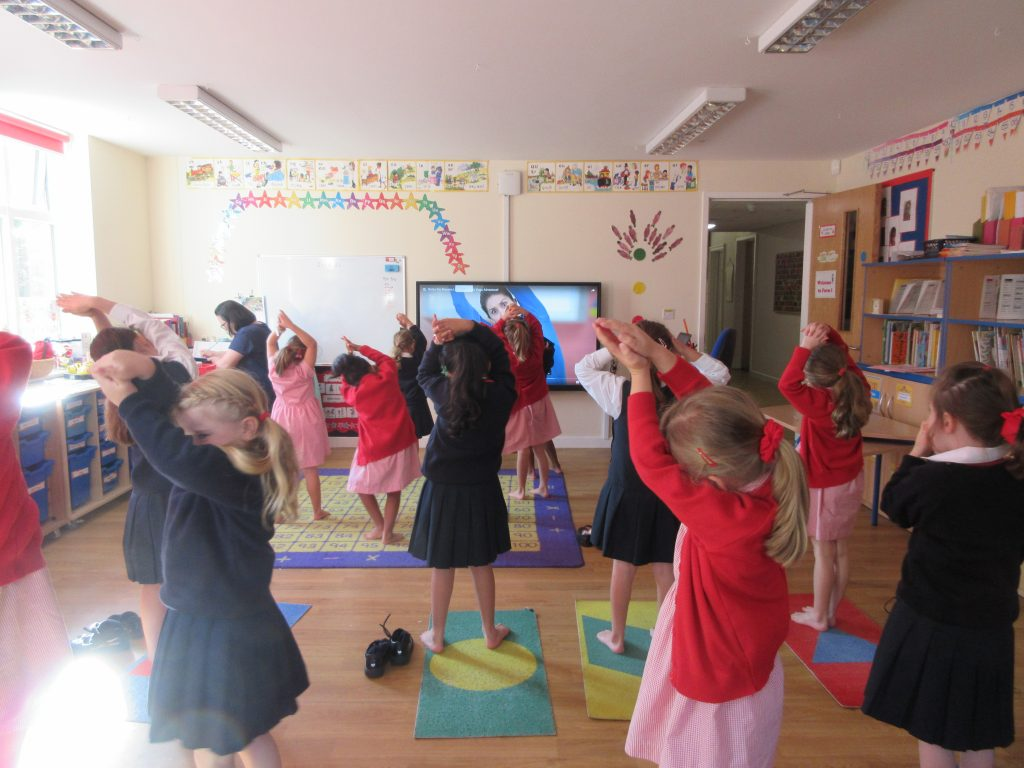 School girls following a video in order to complete an exercise