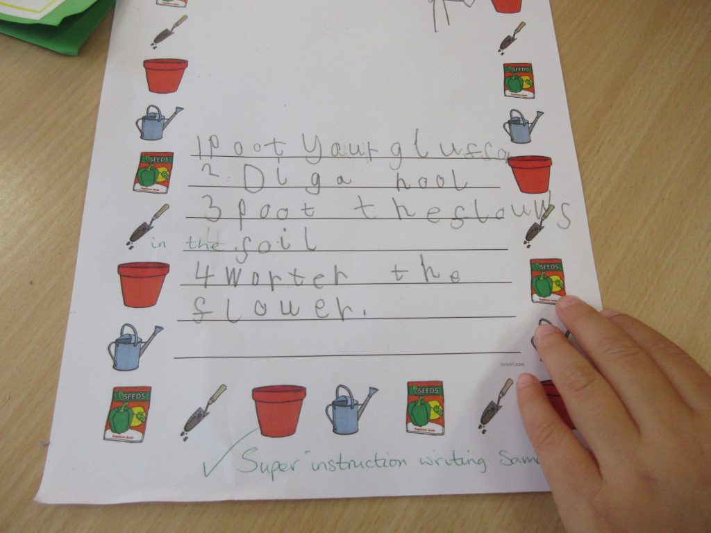 Children writing instructions for how to maintain a plot of plants