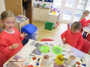 School girls painting different coloured eyes
