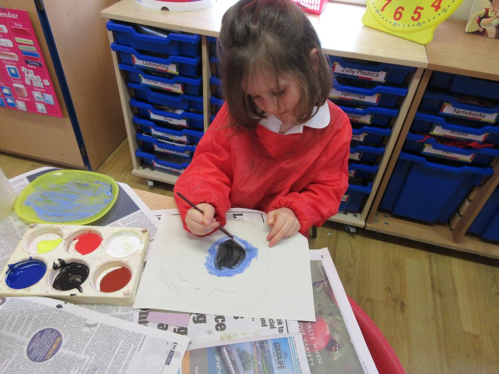 A school girl is painting to the colour of her own eye